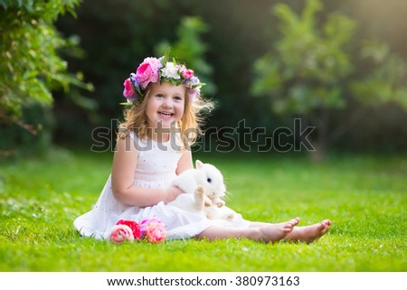 Girl playing with real rabbit in sunny garden. Child and bunny on Easter egg hunt in flower meadow. Toddler kid feeding pet animal. Kids and pets play.  Fun and friendship for animals and children. - stock photo