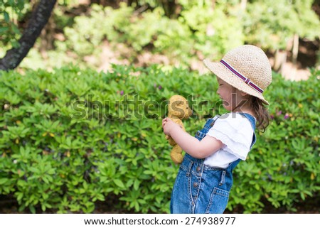 Girl playing with teddy bear - stock photo