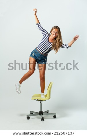 Girl plays the fool standing on chair balancing - stock photo