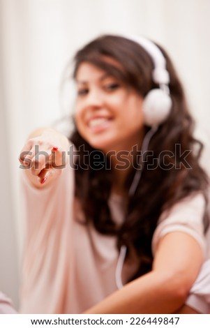 girl pointing out her finger to you while listening music - stock photo