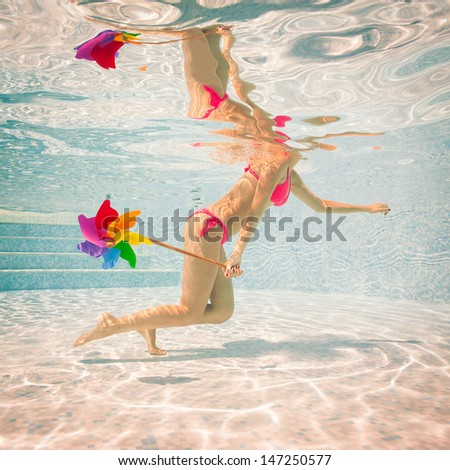 Girl portrait underwater with pink bikini and windmill in swimming pool.  - stock photo