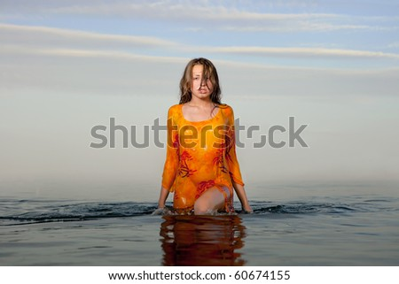 girl posing in the Water at sunset, real water, not photoshop-effect - stock photo
