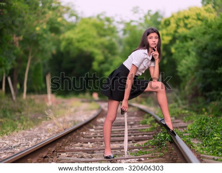Girl posing on the railway line - stock photo