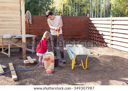 girl pours water in a bucket of cement to help dad - stock photo