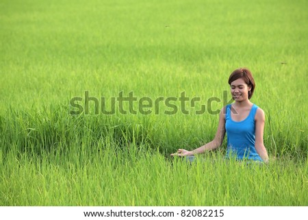 girl practicing yoga in paddy field. - stock photo