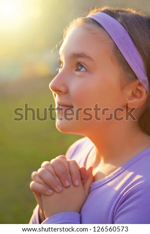 Girl praying with opened eyes at sunset light - stock photo