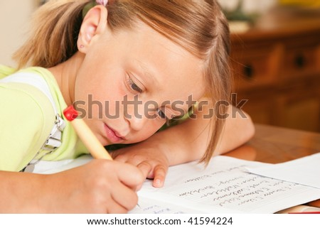 Girl preparing her homework for school writing in her exercise book - stock photo