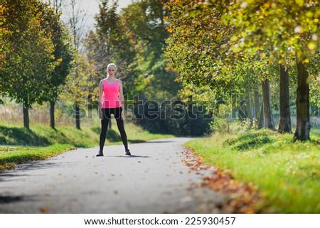 Girl preparing to run at sunny day - stock photo
