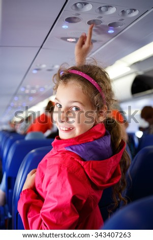 girl presses a button on the ceiling of the plane - stock photo