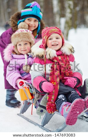 Girl pushes sledges with two younger children in winter park - stock photo