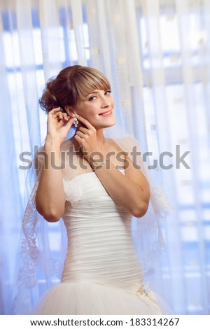 girl puts on an earring - stock photo