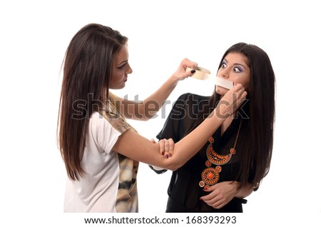 Girl putting duct tape over her friends mouth - stock photo