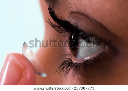 Girl putting on her contact lens - stock photo