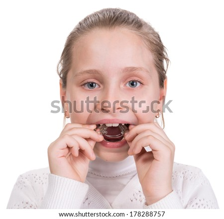 Girl putting on  medical braces for orthodontic treatment over white - stock photo