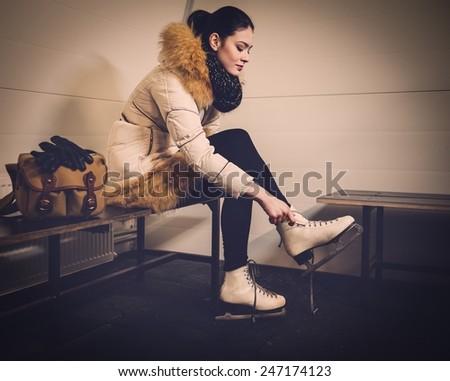 Girl putting on skates  in locker room - stock photo