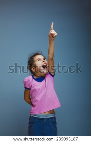 girl raised her thumbs up shouting on gray background - stock photo