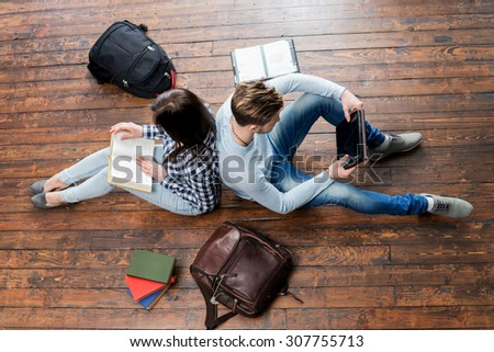 Girl reading a book and boy using a tablet leaning on each other on wooden floor having notebooks and bags around them.   - stock photo