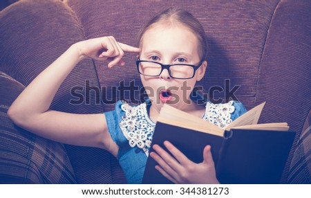 Girl reading a book at home sitting in an armchair. Photos in retro style. - stock photo