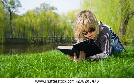 girl reading a book lying on the grass - stock photo