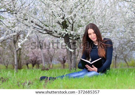 Girl reading a book sit on the grass - stock photo