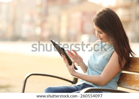 Girl reading and browsing an ebook or a tablet sitting in a bench in a park - stock photo