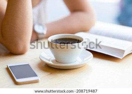 Girl reading book and drinking coffee at cafe - stock photo
