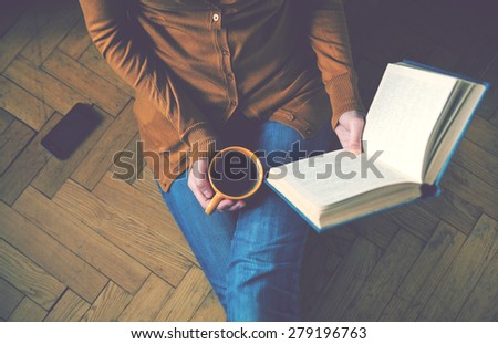 girl reading book and drinking fresh coffee - stock photo