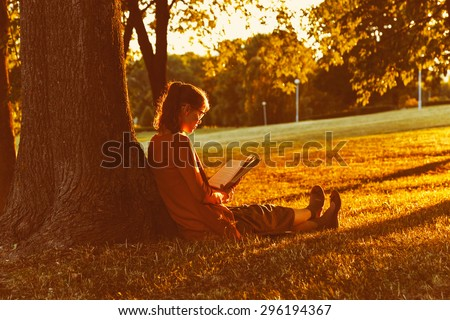 girl reading book at park in summer sunset light - stock photo