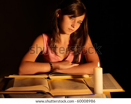 Girl reading book with candle. Black background. - stock photo