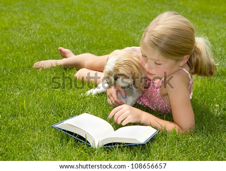Girl reading with pet dog outdoors in the grass - stock photo