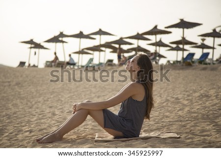 girl relaxes on a beach at a resort in background beach umbrellas - stock photo