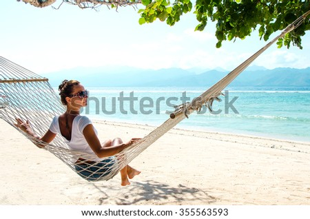 Girl relaxing in hammock on the beach near blue ocean. Bali, Indonesia. Stock image. - stock photo