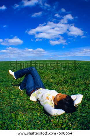 Girl relaxing on a field of grass. - stock photo