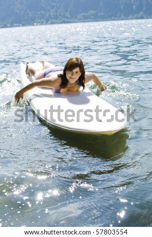 Girl relaxing on surfboard at the lake of Zell am See, Austria - stock photo