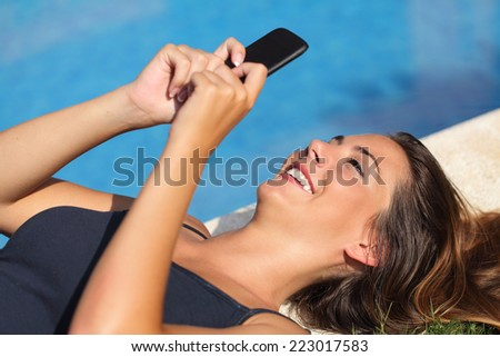 Girl resting and texting on a smart phone on an hotel poolside on vacations with water in the background - stock photo