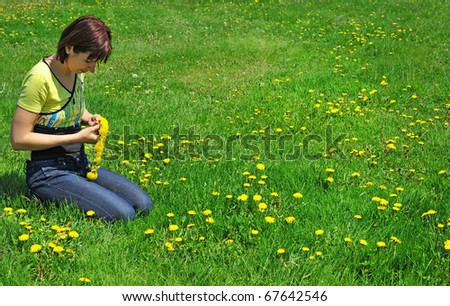 girl resting on the green meadow with   dandelion flowers - stock photo