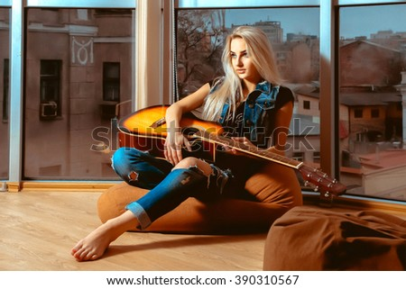 girl resting with a guitar in her hands near the large windows with city views. Girl with guitar. Woman playing guitar. leisure with guitar. - stock photo