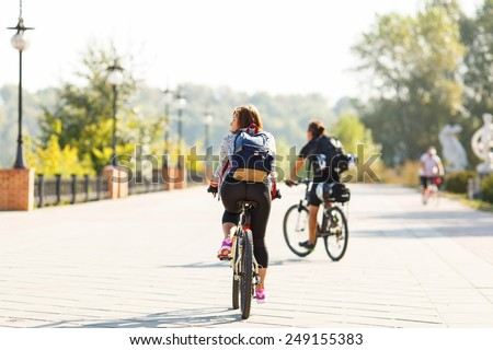 Girl rides a bicycle. Cycling. Road for cyclists. A woman riding a bicycle on a background of blurred silhouettes of other cyclists. Walk on a bicycle in the nature park on the road. Active lifestyle - stock photo