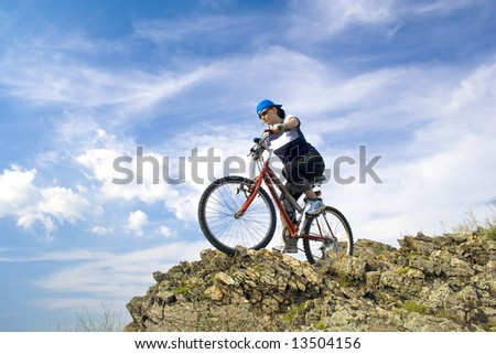 Girl rides a bike in mountains. - stock photo