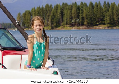 Girl riding a motorboat on a beautiful lake - stock photo
