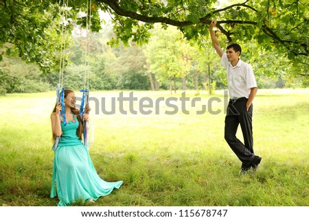 Girl riding on a swing, the guy standing beside her - stock photo
