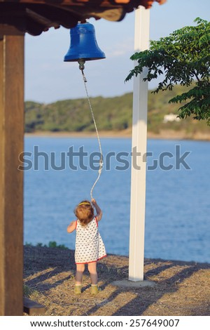 girl ringing in blue bell at sunset - stock photo