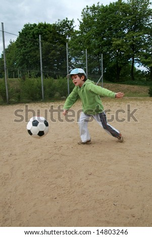 girl run to football on the sand playing field - stock photo