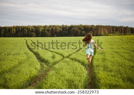 Girl running along a path in a field at sunset - stock photo