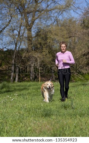Girl running through the woods with your dog - stock photo