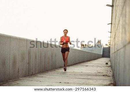 Girl runs along the concrete wall at sunset, wearing heart rate monitor - stock photo