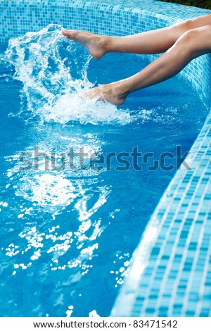 girl's beauty legs in the pool making splashes - stock photo