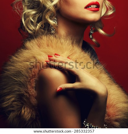 Girl's best friends and femme fatale concept. Marilyn Monroe style. Portrait of rich young woman wearing expensive luxurious diamond accessories, furs. Studio shot - stock photo
