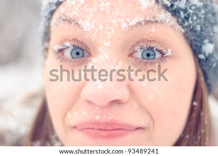 Girl's face under snow outdoors. Close up portrait - stock photo