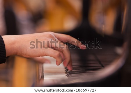 Girl's hand on the keyboard of the piano - stock photo